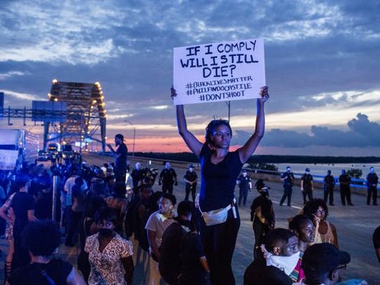 Chanel Trice holds a sign while standing on the median of the Interstate 40 bridge over the Mississippi River. Black Lives Matter supporters brought traffic to a standstill on both sides of the bridge by about 7 p.m. as the estimated crowd on the bridge swelled to more than 1,000.