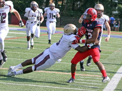 Stepinac's DeVante Reid tries to avoid a tackle during his team's 48-6 victory over Iona Prep at Stepinac High School on Sept. 19, 2015.