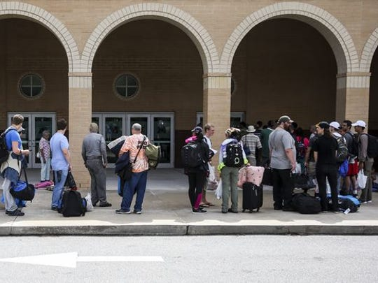 People line up to check into a shelter at Mainland