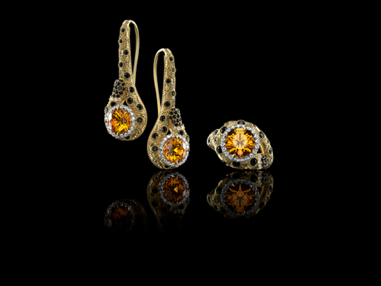 "Eye of the Cheetah from the Chestora Collection: A $20,000 ""Eye of the Cheetah"" 18k yellow gold ring and earring set, which features. The set is encrusted with over 190 black and white diamonds."