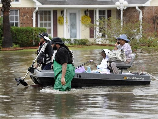 A photo from Aug. 13, 2016 shows men rescuing a woman and a child in a boat in Baton Rouge, Louisiana.