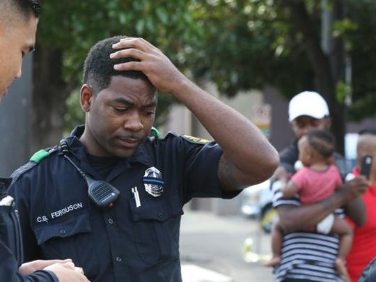 A Dallas police officer reacts to the sniper attack on July 7, 2016, that killed five officers and wounded 12 others.