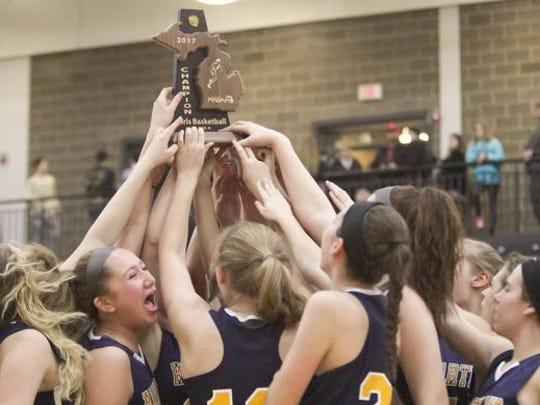 The Hartland girls basketball team celebrates its district