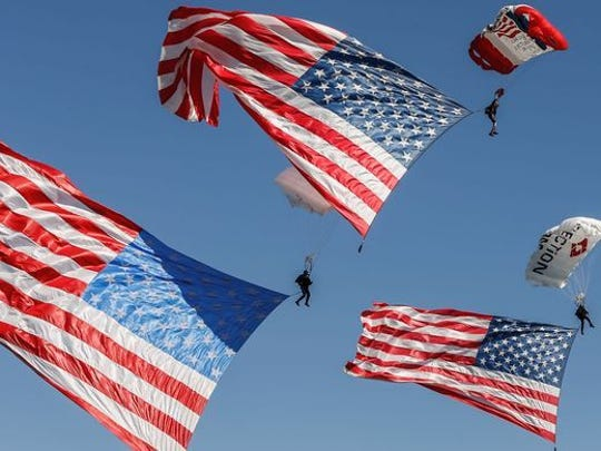 Parachutists fly over Lakota West's football field during the 2015 funeral service for Army Master Sgt. Corey Hood. Hood, 32, a Lakota West graduate and member of the Army's Golden Knights parachute team, died Aug. 16, 2015, following a performance at the Chicago Air and Water Show.