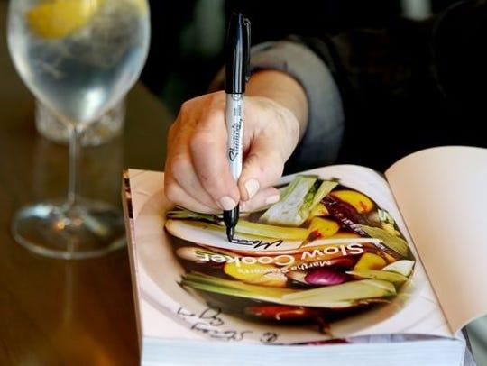 Martha Stewart signs a copy of her newest cookbook,