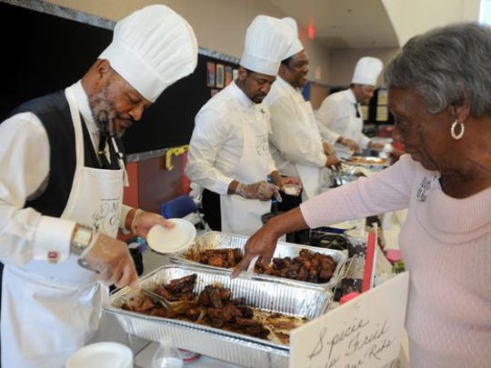 John Johnson, left, serves deep fried ribs to Veola Spann during the 2016 Men Can Cook event in Oxnard. The fundraiser will return Oct. 21 at the Oxnard Performing Arts Center.