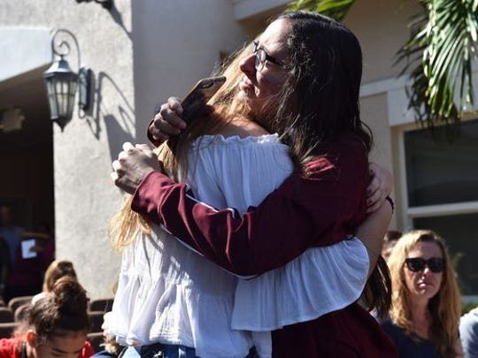 Friends embrace before vigil for Florida school shooting victims.