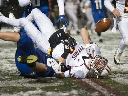 Gibson Southern's Morgan Rexing (2) is taken down by Bishop Chatard's David Marsh (60) resulting in one of eight fumbles in the first half of the 3A semistate football game held at Lawrence North High School on Saturday, Nov. 21, 2015