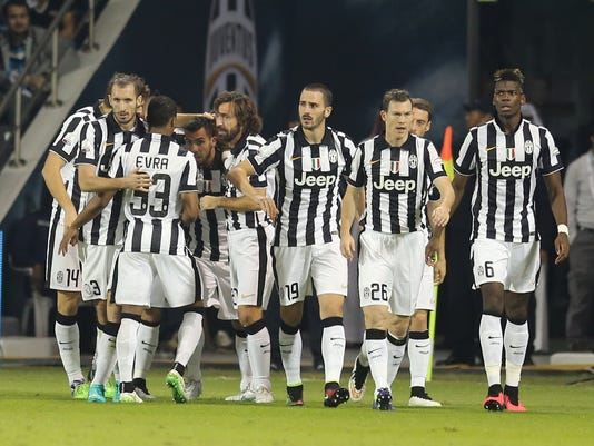 Juventus' forward Argentinean Carlos Tevez, center left, celebrates with teammates after scoring during the Italian Super Cup final match Napoli against Juventus in Doha, Qatar, Monday, Dec. 22, 2014. (AP Photo/Osama Faisal)