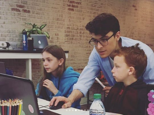 Michael Olaya helps some students during Dexter Learning's first computer programming class.