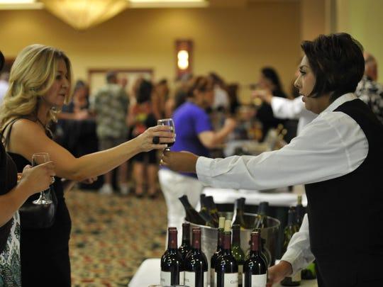 Denise Vargas, right, serves wine to Jen Brandt and