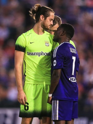 Louisville City's Kadeem Dacres stands up to a taller Shawn Ferguson of Charleston as the two exchange words Saturday night. The match ended in a draw 1-1.