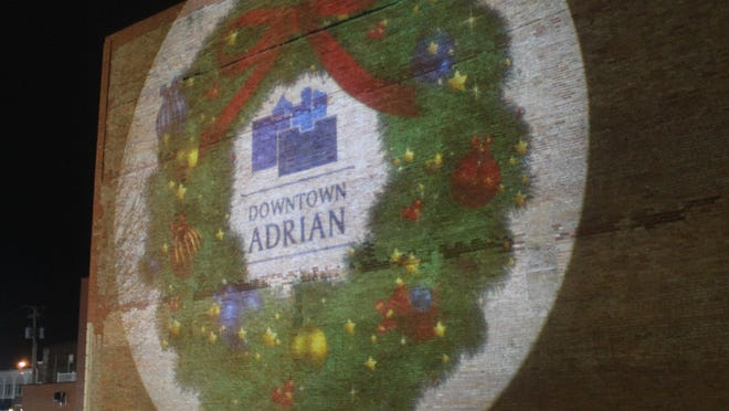 A projector recently installed downtown features holiday- and Christmas-themed images on the wall where the Jean Christopher building once stood at the corner of Maumee and Winter streets.