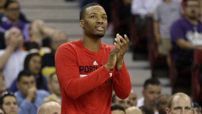 Portland Trail Blazers guard Damian Lillard applauds the action on the court during the third quarter of an NBA preseason basketball game against the Sacramento Kings  in Sacramento, Calif., Saturday, Oct. 10, 2015.   The Kings won 94-90.