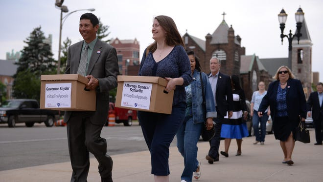 MEA Board of Directors member and Novi teacher Tom Brenner, left, and Hamtramck teacher Michelle Cook make their way to deliver a box of petition signatures to Gov. Rick Snyder's office in the George W. Romney Building on Thursday, June 23, 2016.