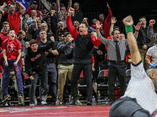 Rutgers wrestling coach Scott Goodale (center) and fans celebrate Phil Bakuckas' pin of Michigan's Aaron Caldron at Rutgers' Louis Brown Athletic Center on Sunday.