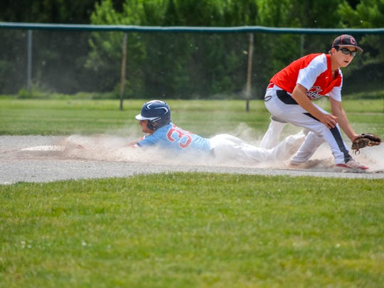Sliding head-first into second base during Saturday's district final at Dearborn is Livonia Franklin's Johnny DiPonio.
