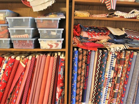 A stack of patriotic-themed fabrics waits for quilters in Anderson.