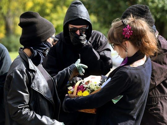 Antifa members stop to get a flower from Jamie Braman,