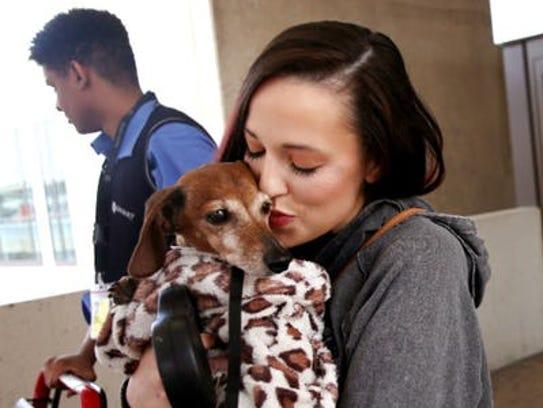 Donna Rosen kisses her dog Bobo while waiting for an