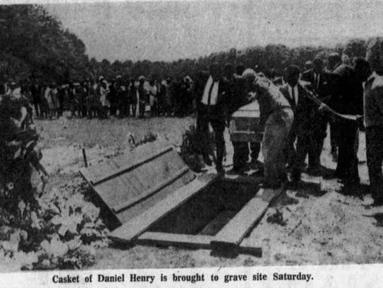 The casket of Daniel Henry is brought to the gravesite.