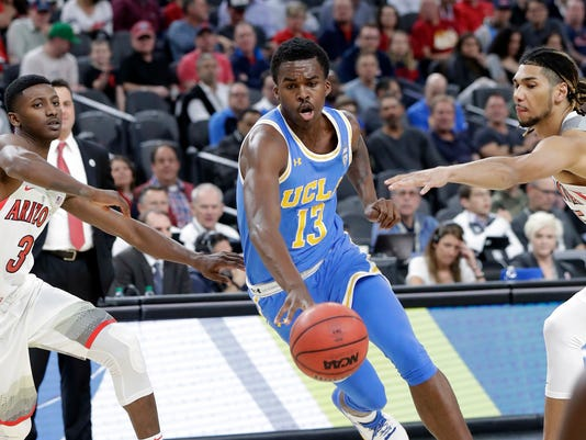 UCLA's Kris Wilkes (13) drives between Arizona's Dylan Smith (3) and Keanu Pinder (25 during the first half of an NCAA college basketball game in the semifinals of the Pac-12 men's tournament Friday, March 9, 2018, in Las Vegas. (AP Photo/Isaac Brekken)