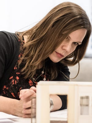 """Playwright Laura Eason, seen here looking at a set model, wrote the adaptation of Mark Twain's """"The Adventures of Tom Sawyer"""" that runs Nov. 17-Dec. 9 at the Cincinnati Shakespeare Company."""