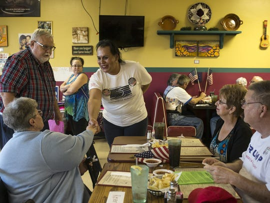 "Ernest McCollum (left, standing) introduces Joanne Selena Lopez Cervantez (center, standing) to attendees of a ""Believers in Trump"" meeting in Wickenburg. Cervantez is running as an independent for U.S. Senate, trying to become the first transgender and Latina Senator."