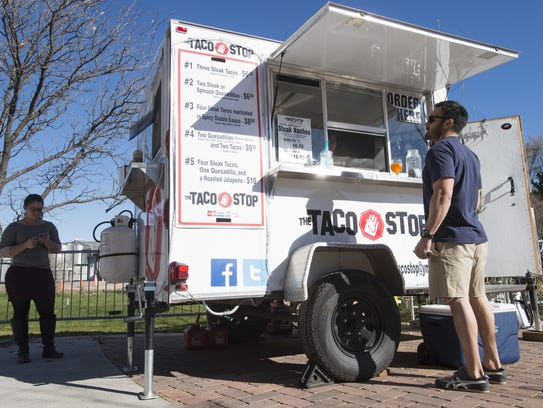 Customers order food from the Taco Stop, parked on