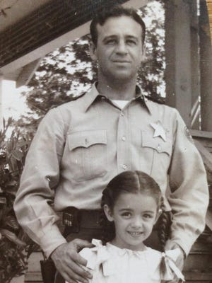 Holly Holcomb with his daughter, Sue, on his first day back to work with Oregon State Police after returning from serving as a pilot with the Army Air Corps during World War II.
