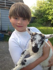 Austin Hester with a lamb in 2014 on the Hester family farm in Westport, Ireland
