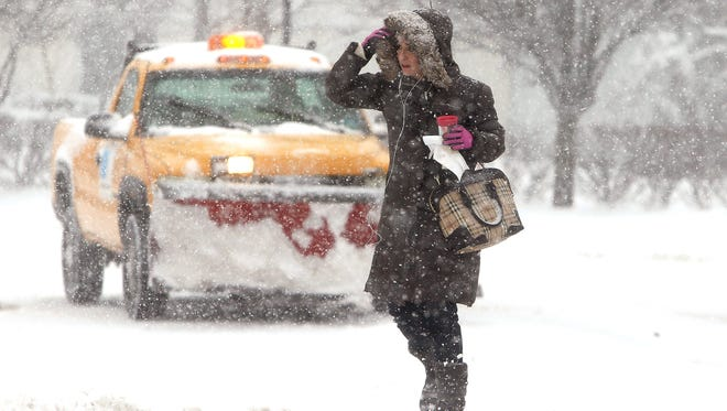 Erica Linfante of Morristown crosses the street at the Morristown Green as the first winter storm of the season is predicted to drop more than a foot of snow in parts of New Jersey.   February 9, 2017, Morristown, NJ.