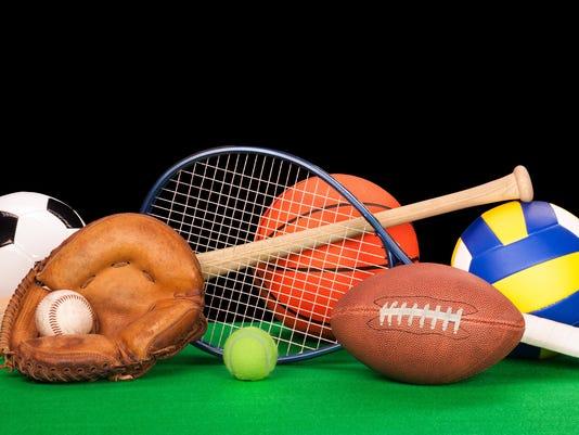 Arrangement of assorted sports equipment on black background