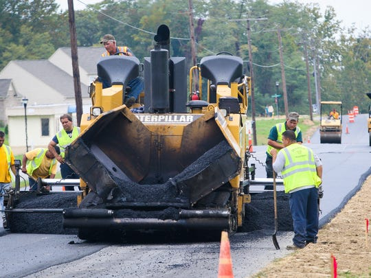 Construction workers work on paving a stretch of road along Railroad Avenue at the Townsend Villages II neighborhood Tuesday, Oct. 11, 2011.