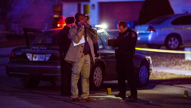 IMPD detective talks on the phone at the scene of a fatal shooting in the 4400 block of Roberton Blvd. Jan. 29, 2015
