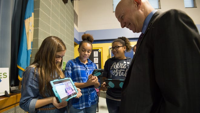 Sixth grader, Mia Barone, shows a recycling video to Governor Jack Markell after an assembly at H.O. Brittingham Elementary School in Milton.