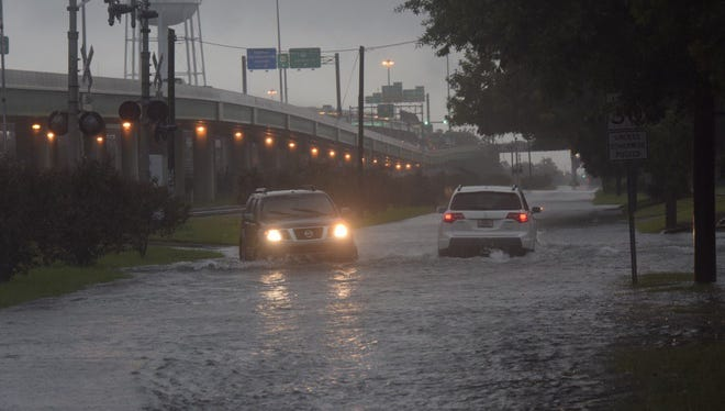 Heavy overnight and early morning rain fill roadways in downtown Pensacola.