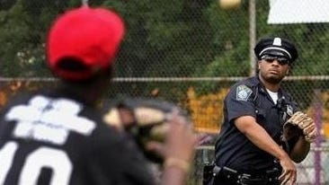 A new playground at Belcher Park will be named for DJ Simmonds, shown playing catch with a Boston youth, who died as a result of injuries sustained in the Boston Marathon bombing manhunt.