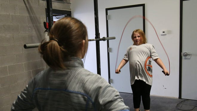 Exercise physiologist Missy Sachs, left, watches Katherine Phinney, 9, jump rope during a prime class at the Louisville Youth Training Center.  Phinney has been able to halt excessive weight gain with the classes.Mar. 22, 2016