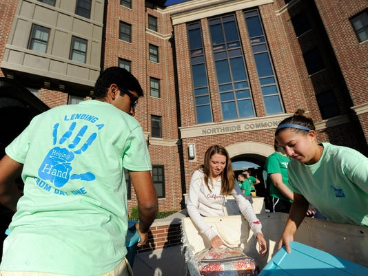Abhi Kudaravalli, left, and Amanda Sherry, right, members of the York College Move-In Team, help Jessica Leming-Lawton, center, of New Jersey, move into her new dorm room.