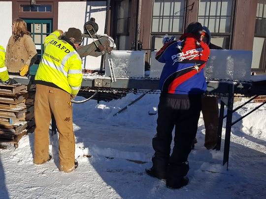Volunteers feed 80-pound blocks of ice through a shaver