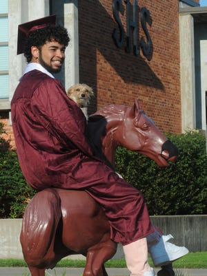 Salina Central graduate Mosés Brown on the Mustang statue while holding his dog Nani, a Chihuahua and Terrier mix, after receiving his diploma during the drive-through graduation in the Salina Central parking lot on Saturday morning.