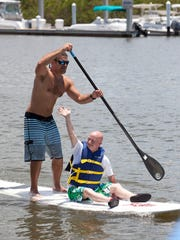 Brian Francis of Naples waves to cheering crowds as teammate Mike Bono of Marco Island paddles during the Special Olympic Athlete Race where a Special Olympian is paired with one of the top 14 to place in the men's division race during the 2nd annual Stand Up Paddleboard Luau Races held at Bayfront Marketplace and Marina in Naples on May 21, 2011.