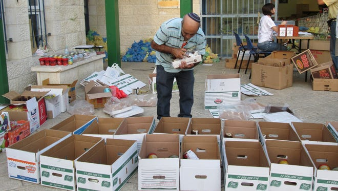 Volunteers with the Shachen Tov (Good Neighbor) program pack cartons of food to be distributed to needy Israelis for the start of the Jewish new year.