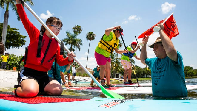 Natalie Pernia, 18, from Manatee County, waits for the start flag from Tom Navin during the Special Olympics Florida Area 9 Standup Paddle Competition on July 14, 2018 at Sugden Regional Park in Naples. Special Olympics provides year-round sports training and competition to children and adults 8 years of age and older with intellectual and developmental disabilities.