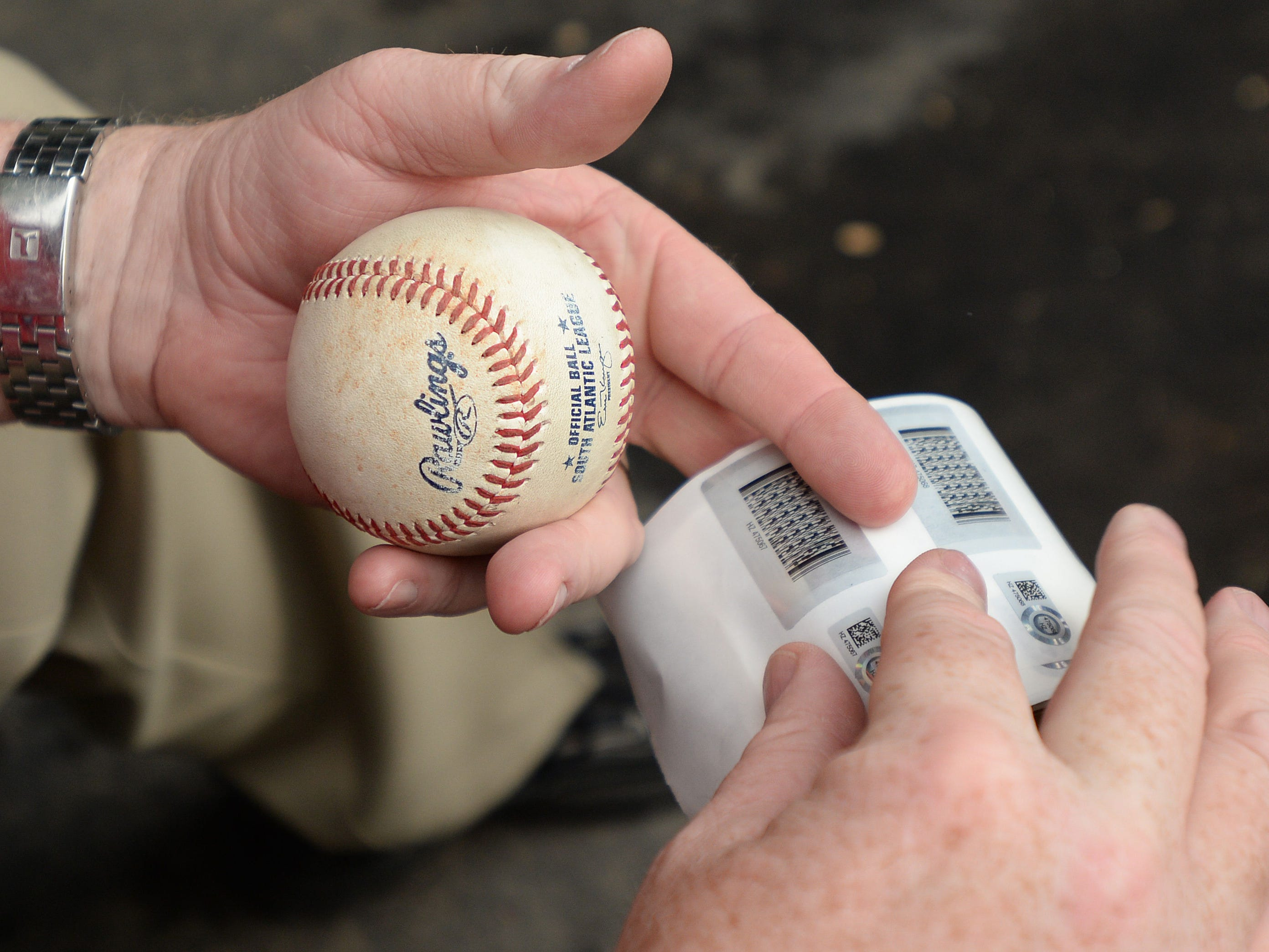 A MLB authenticator logs and places a sticker for identification on the ball from the Greenville Drive's Yoan Moncada (24) first at bat as a Greenville Drive Monday, May 18, 2015.