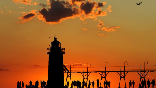 (ROD SANFORD PERSONAL PHOTO)  Vacationers and tourists watch the sunset over Lake Michigan from the pier and lighthouse in South Haven, Michigan in August 2011. (photo by Rod Sanford)