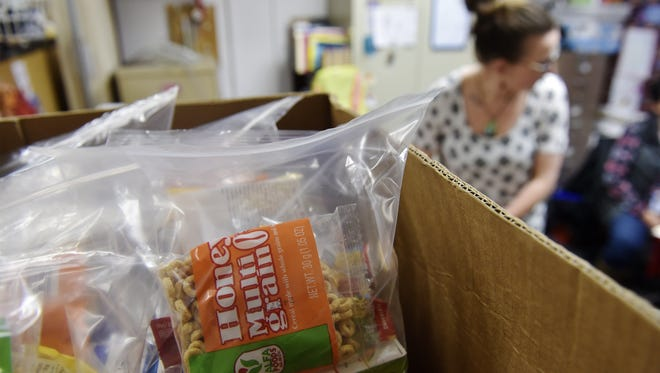 Liz Pipinich, Family Engagement Advocate at Whittier Elementary School, prepares food bags for students in the Backpacks4Kids food program.  The program provides students with food to take home over the weekend and is run by the Great Falls Community Food Bank and the Great Falls Elementary School District