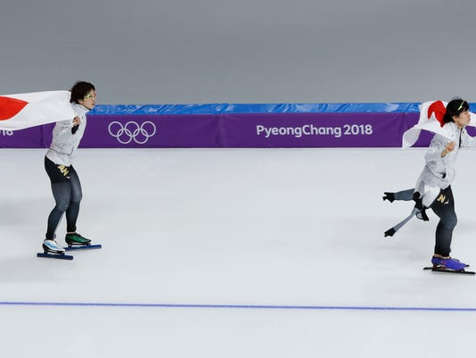 Japan's Nao Kodaira, left, silver medal, and Miho Takagi, right, of Japan, bronze medal, skate with the national flag after the women's 1,000 meters speedskating race at the Gangneung Oval at the 2018 Winter Olympics in Gangneung, South Korea, Wednesday, Feb. 14, 2018. (AP Photo/Eugene Hoshiko)