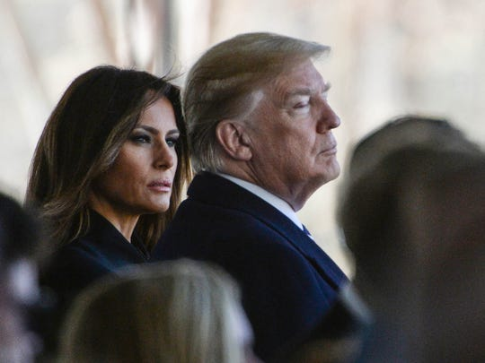U.S. President Donald Trump, right, and Melania Trump watch the family walk in for the private funeral service for Billy Graham in a tent outside the Billy Graham Library in Charlotte, N.C. on Friday, March 2, 2018.